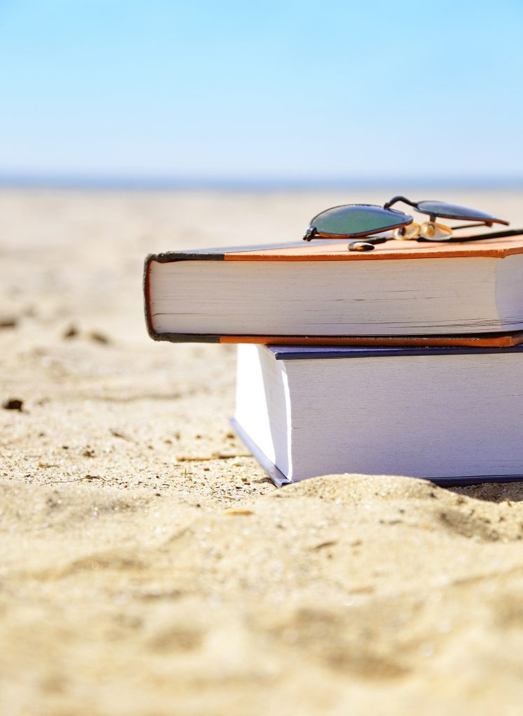 Books on sandy beach with sunglasses
