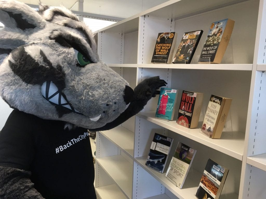 Image of CityWolf looking at books on Wolf-themed topics, e.g. Wolf Hall