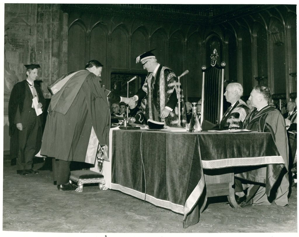 Landscape image of a man in full academic dress stooping in front of a table (back to camera at an angle), shaking hands with another man in academic dress who is standing facing him: two other men in academic dress are sat at the table to the man standing's left. A man is stood further away in the background to the left (also in cap and gown) watching, and there are smartly dressed people sat in rows behind.