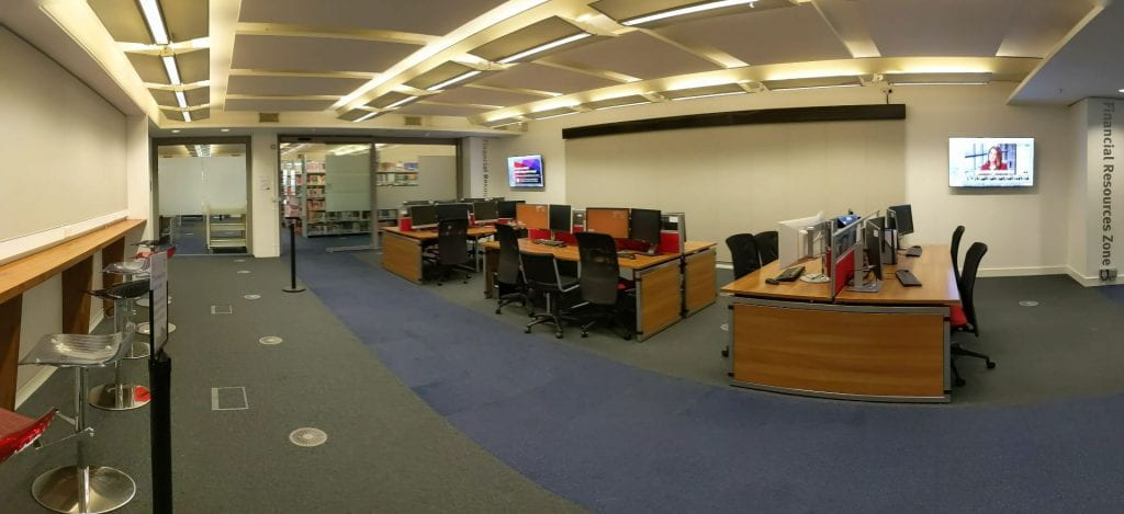 Panoramic image of a library space with three blocks of four computers, underneath a ticker and two video screens. The colour scheme is grey, brown and teal.