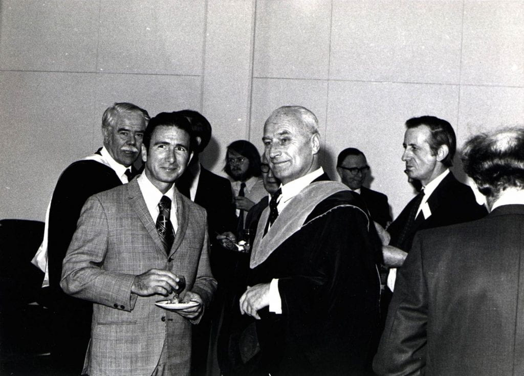 Colonel James Irwin (centre left) and Professor Grigory Tokaty (centre right) and at the reception for the Apollo 15 astronauts at City in 1971. Various other figures stand behind the two men.