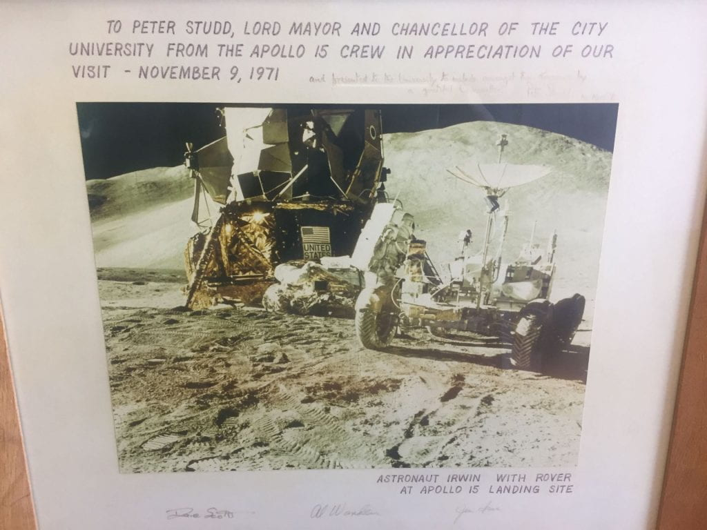 "The signed photo of the Apollo 15 landing module and rover presented by the Apollo 15 astronauts. The inscription reads: ""To Peter Studd, Lord Mayor and Chancellor of the City University from the Apollo 15 crew in appreciation of our visit - November 9, 1971"" and the caption reads: ""Astronaut Irwin with rover at Apollo 15 landing site."""