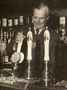 Alan Loader Maffey, 2nd Baron Rugby, Master of the Saddlers Company, pulling the first pint in the new Saddlers' Bar, 1978. The pump handles feature horse's heads, in honour of the Saddlers. Source: City News (30 Oct 1978)