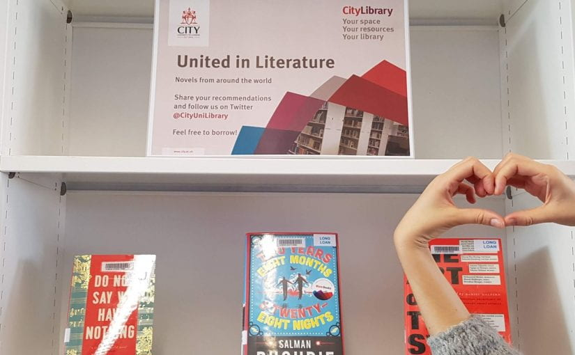 "An image of a past book display of fiction books at Northampton Square Library, entitled ""United in Literature"", along with hands forming a heart symbol"