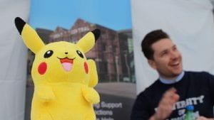 Pikachu plush and a man smiling