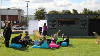 Students sitting on multi-coloured bean-bags outside temporary bar