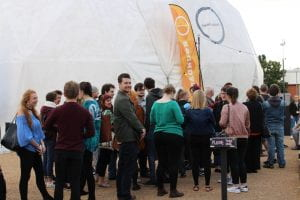 Students queuing for a play in a temporary performance space