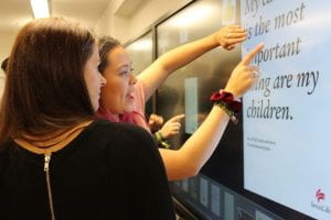 Two female students pointing at an interactive whiteboard