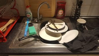 Pile of dirty plates in a sink.