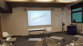 Large white board displaying Group Project in empty class room.