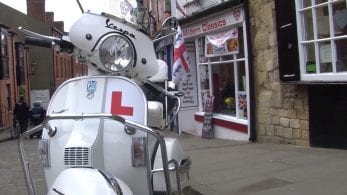 White vespa with Learner plates, parked in front of Modern Classics shop front.