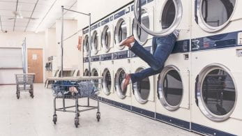 Laundry room, with a person leaning in to a washing machine.