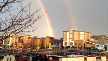 Two rainbows, above buildings and boats across the Brayford Pool.