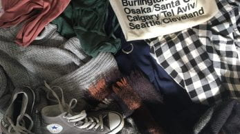 Pile of clothes, tote-bag and converse shoes.