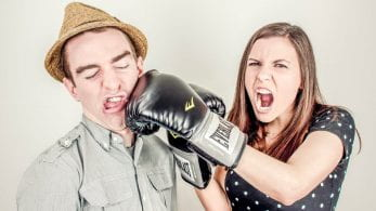 Female wearing boxing gloves, punching male.