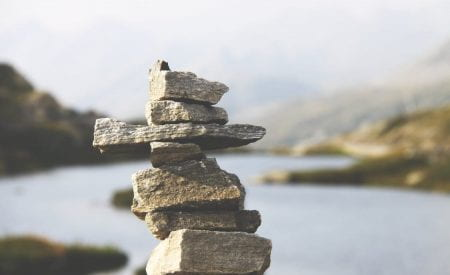 A stack of rocks balancing on top of each other, in front of a blurred river background.
