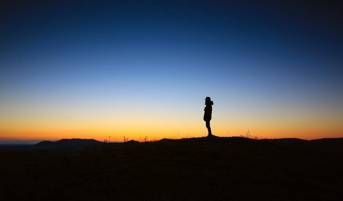 Silhouette of a man on a horizon at sunrise.