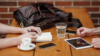 Table with iPads, phones, a cup of water, an espresso and a handbag.