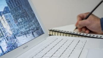 Close up of a MacBook and a person writing in a notebook.