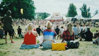 The back of three girls sat facing a stage at a festival.