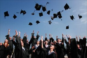 A group of students throwing their graduation caps in the air.