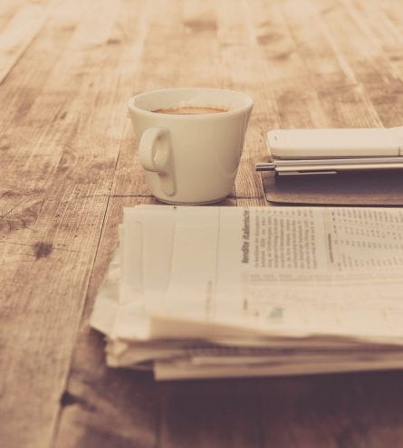 Cup of coffee, newspaper and mobile phone on a table.
