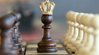 A close up of a chess pawn wearing a king's crown