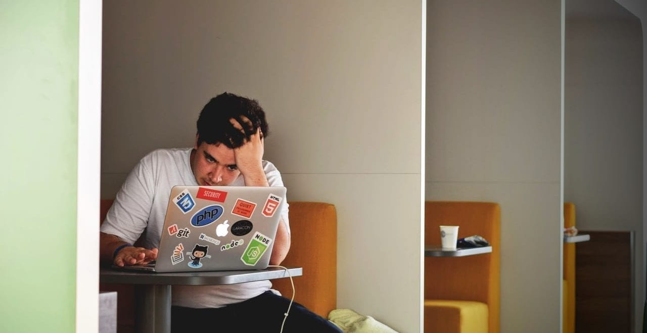 Male student sat in a study space, looking at his Mac laptop.
