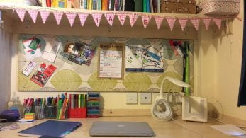 Students desk at home, with stationery and a laptop.