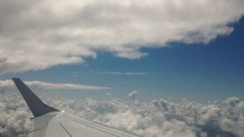View from an aeroplane window, of the wing, above the clouds.