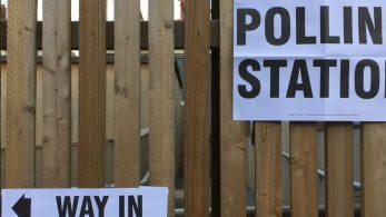 Polling station posters on a fence