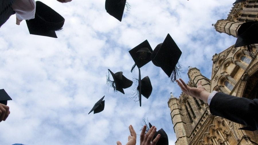 Group of students throwing their graduation caps in the air, shot from below.
