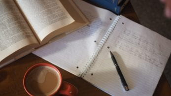 Open notepad and pen, textbook and mug of coffee.