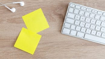 Mac Keyboard, two yellow post it notes and white ear bud headphones.