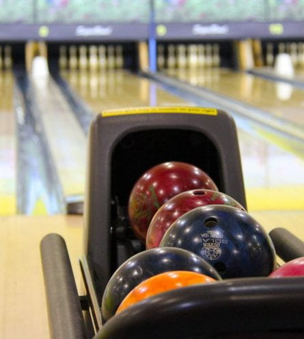 Bowling balls, in front of a row of bowling lanes.