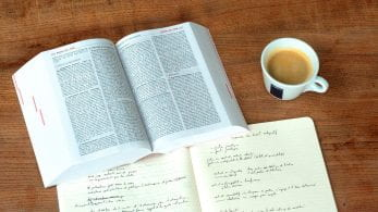 Open text book, notebook and a cup of coffee.