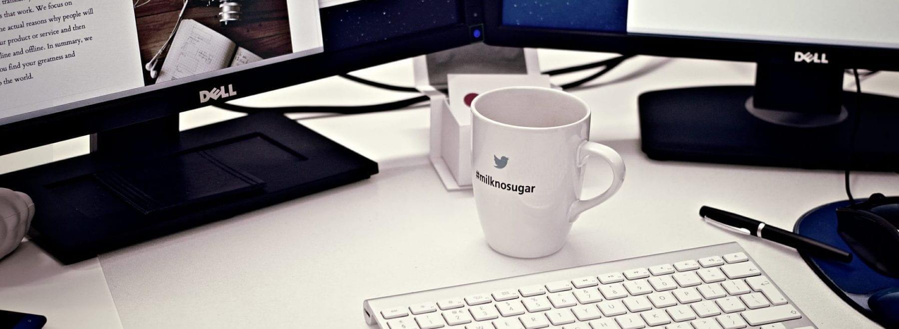 Two computer screes, a keyboard and a mug.