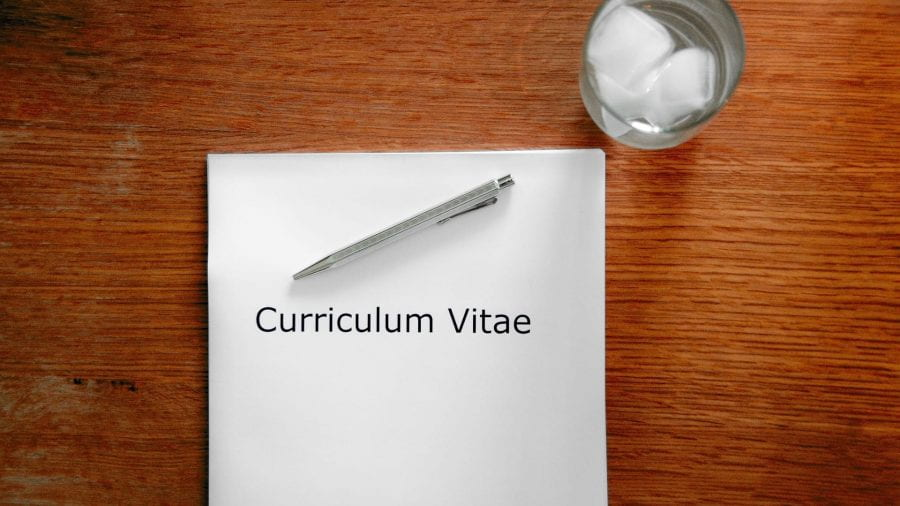 A white piece of paper, with Curriculum Vitae written on it, a pen and a glass of water.