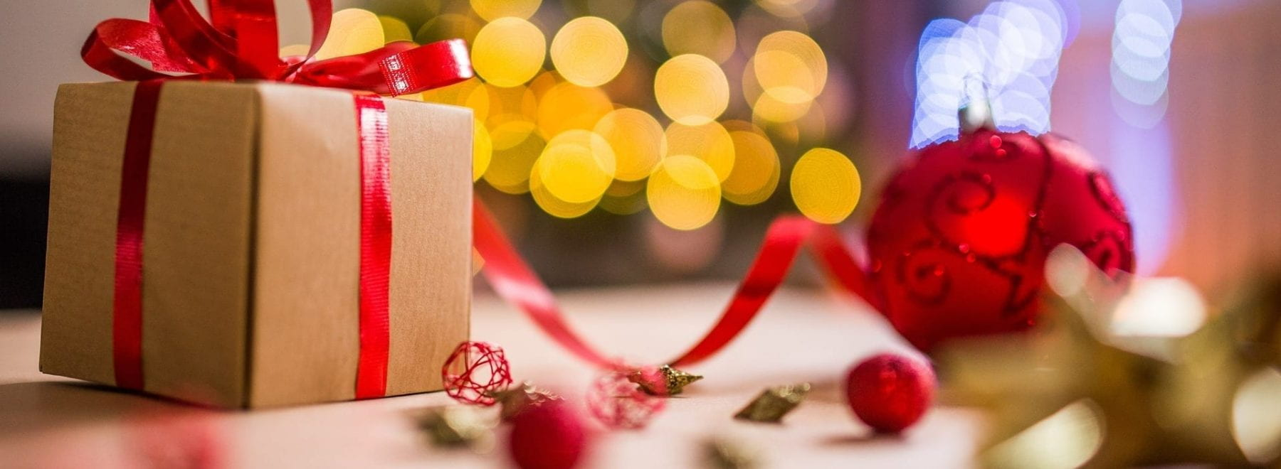 A small Christmas present wrapped in brown paper and red ribbon.
