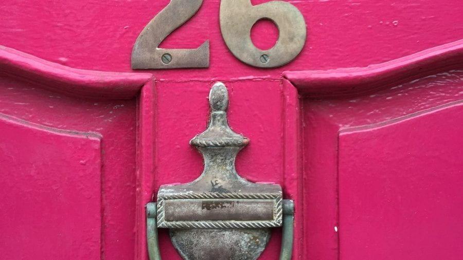 Pink door, with the number twenty six, over a door knocker.