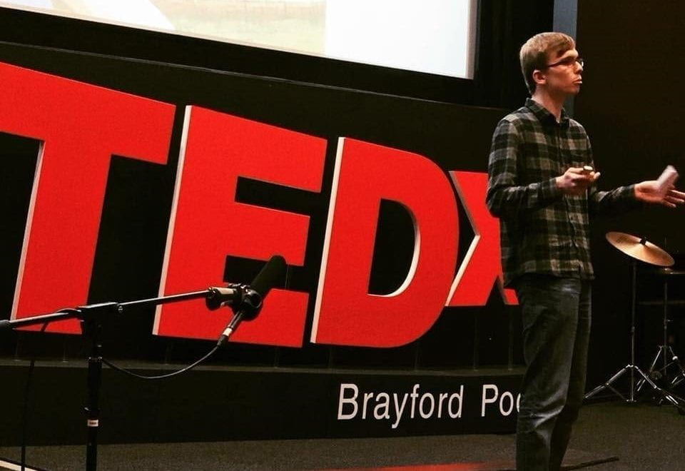Male student standing in front of a TedX sign, delivering a speech.