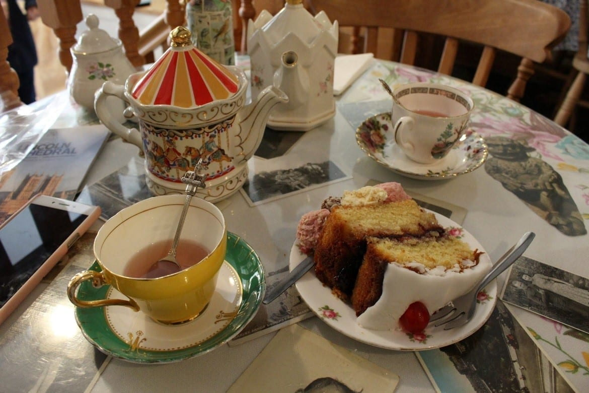 picture of tea and cake with china cups and china cutlery