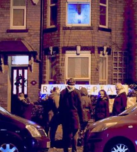 A group of people stand outside of a house watching a projection at night