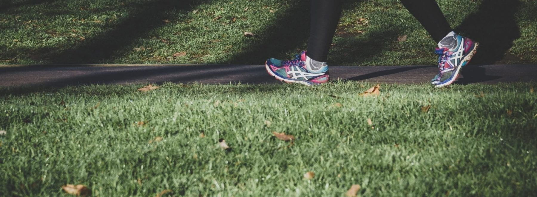 Someone wearing bright running shoes walks along a path with grass on either side