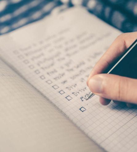 Somebody creates a checklist on grid paper with a pen