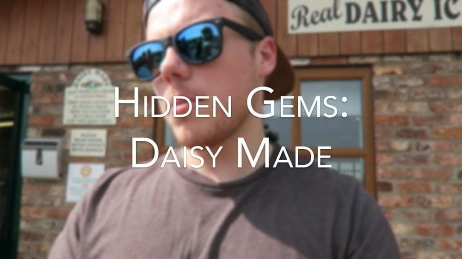 A young man wearing sunglasses stands in front of a building with the caption 'Hidden Gems: Daisy Made'
