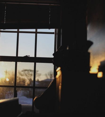 A sunrise silhouettes somebody stood in front of a window