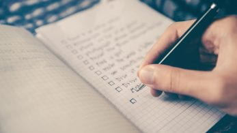 Somebody writes a checklist in a notebook