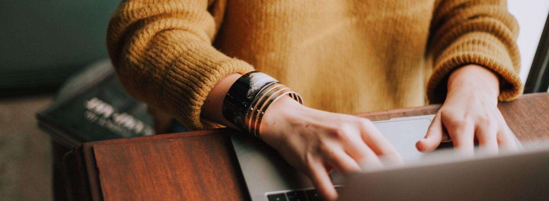 Girl writing on laptop.