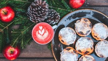 mince pies on a plate and a hot, red drink in a mug. There are decorative apples and pinecones surrounding them.